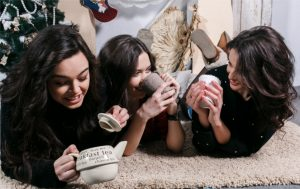 Beautiful girl eating Christmas cookies and drink tea while lying on a carpet. Decorative vintage apartment.