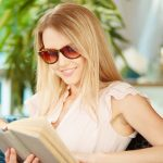 Portrait of cute girl in sunglasses reading a book at leisure